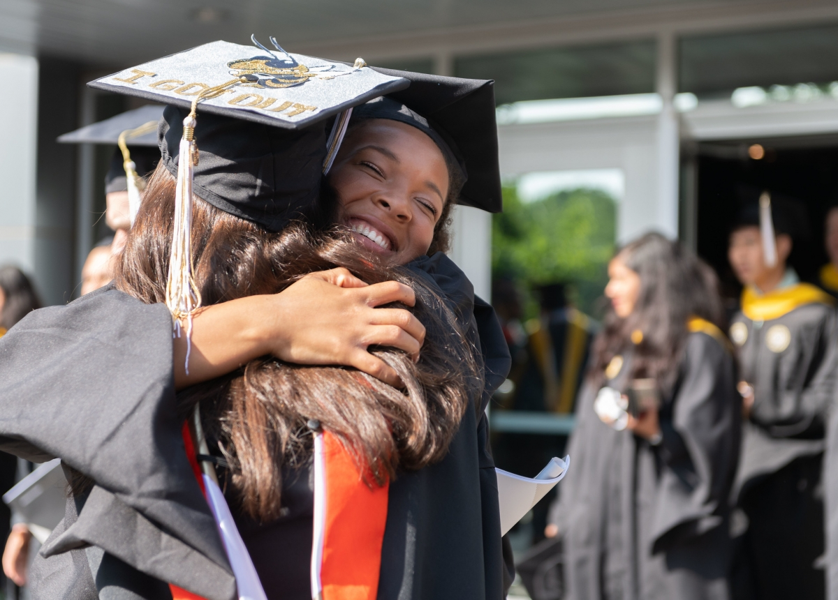 Two young women hug in graduation gowns.