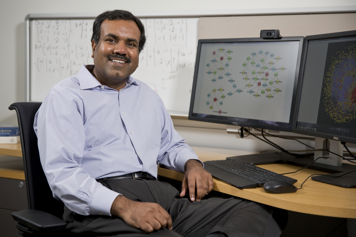 Srinivas Aluru sitting in a computer chair smiling in front of computer and white board