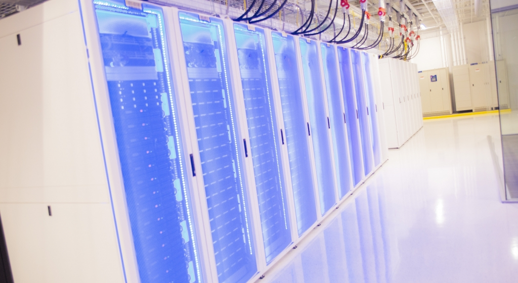 Photograph of a stack of computers with blue LED lights circling their cages in a stark white datacenter.