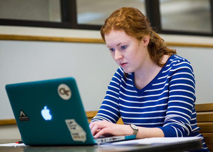 Woman studying in the College of Computing Lobby